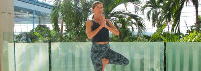 Frau in Yoga Position auf der Sky Lounge mit Ausblick auf das Palmenparadies
