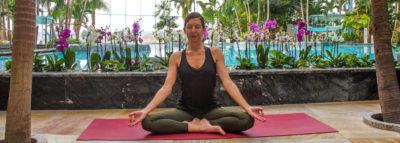 Frau in Yoga Position vor der großen Lagune im Palmenparadies