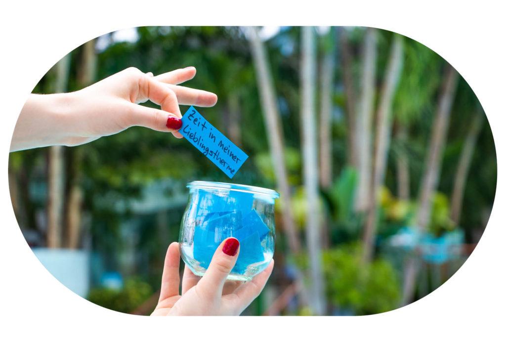 Marmeladenglas mit kleinen blauen Zetteln