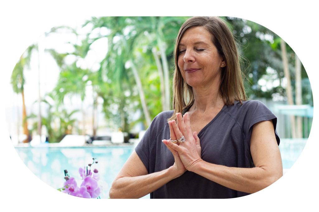 Entspannte Frau mit betenden Händen vor der Lagune