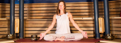 Frau im Schneidersitz bei einer Meditation in der Alhambra Sauna