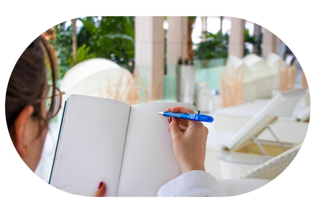 Frau mit Tagebuch und Stift auf einer Relaxmuschel auf der Sky Lounge
