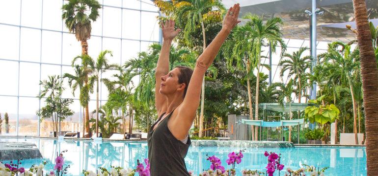 Frau mit Blick nach oben und den Armen über dem Kopf vor der großen Lagune im Palmenparadies