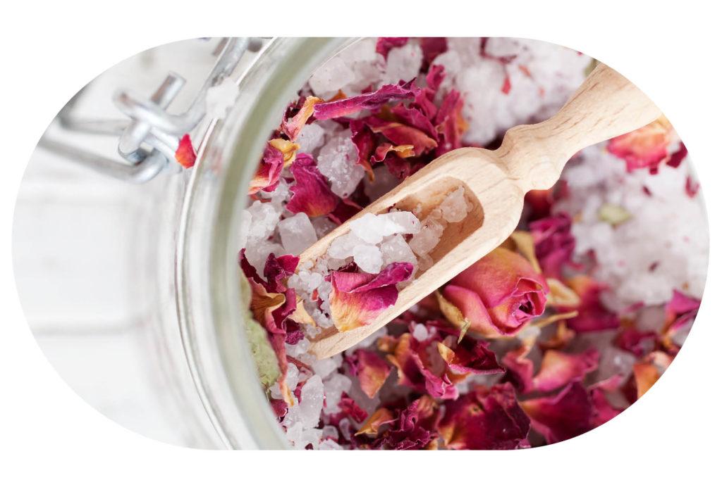 Rosen-Badesalz mit Rosenblättern und einem Holzlöffel