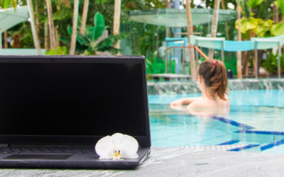 Frau in Whirlpool mit Laptop im Palmenparadies