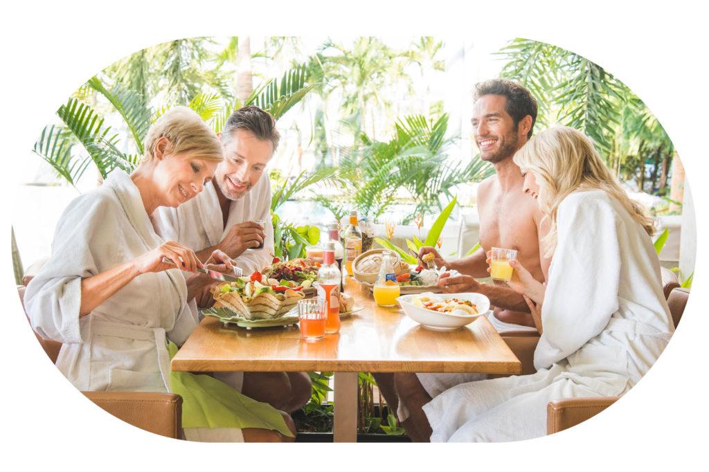 Zwei Paare sitzen an einem Tisch und essen gesunde Gerichte