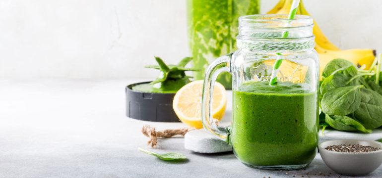 Grüner Smoothie in einem Glas mit Spinat, Zitrone und Banane