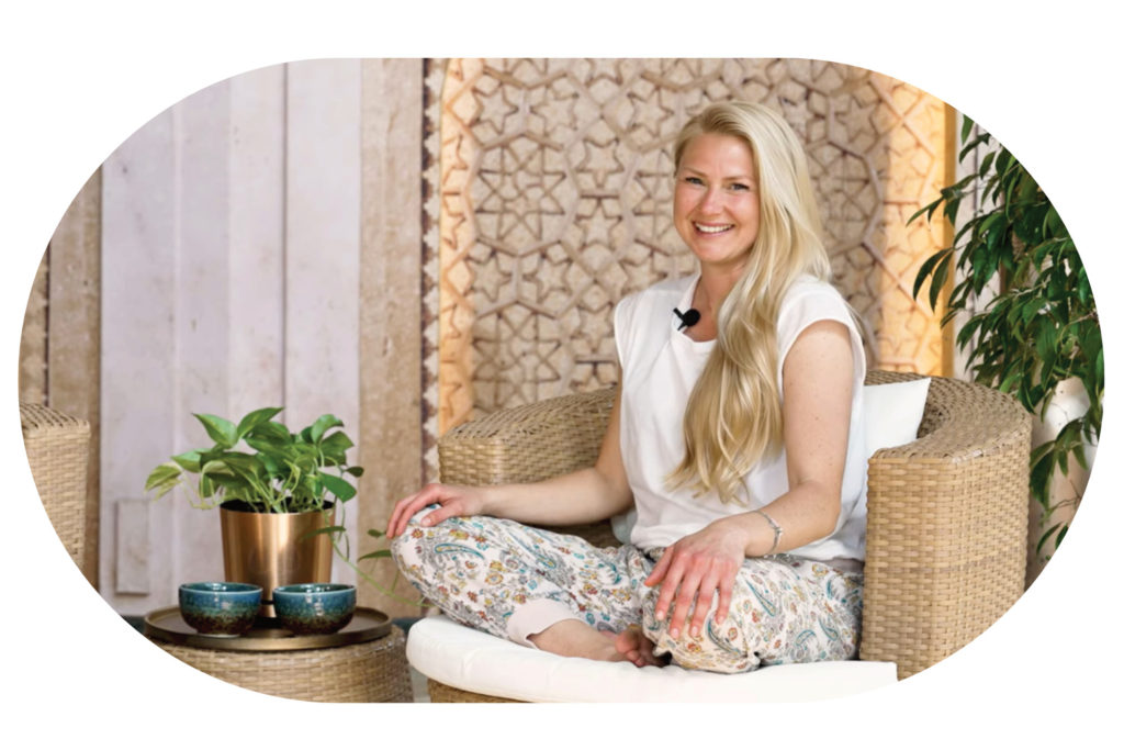 Blonde Frau auf einem Sessel mit Pflanzen