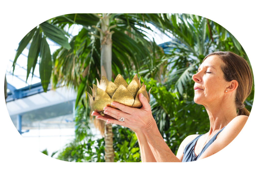 Frau mit goldener Lotusblume vor Palmen