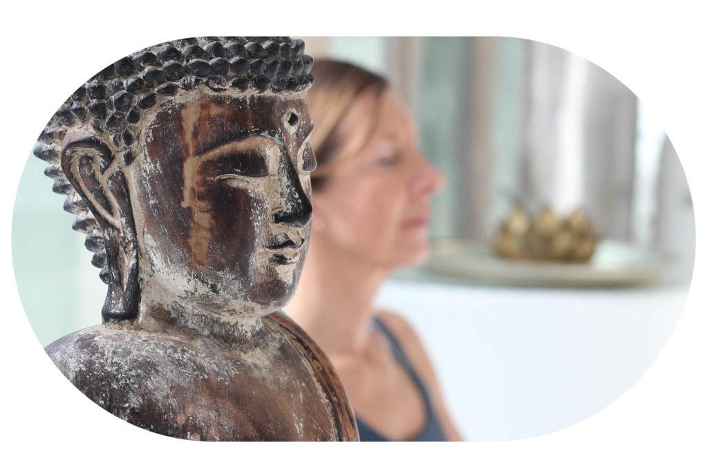 Frau meditiert neben Buddha